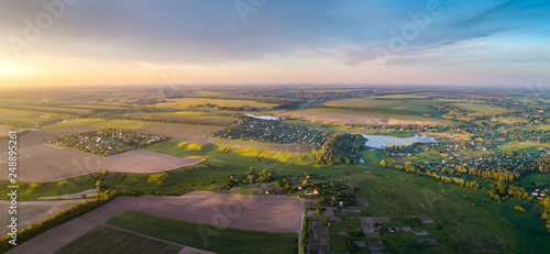 Foto Murales Aerial view of the fresh bright green lush countryside at sunset