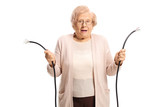 Confused old lady holding a broken cable - 248895484