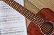 Playing Guitar. Close up view of brown acoustic guitar with music notes against wooden floor