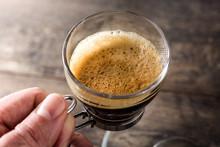 """Постер, картина, фотообои """"Man holding coffee glass and coffee grain on wooden table. """""""