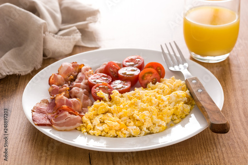 Breakfast with scrambled eggs, bacon, tomatoes,coffee,orange juice ,croissant and corn flakes on wooden table - 248897203