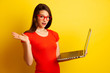 Beautiful student in red tshirt and red glasses holds a laptop over yellow background