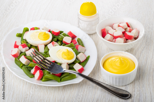Green beans with crab sticks, boiled eggs in dish, mayonnaise, salt, fork on table