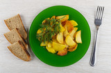Slices of fried potatoes in plate with dill, bread, fork on table. Top view - 248905601