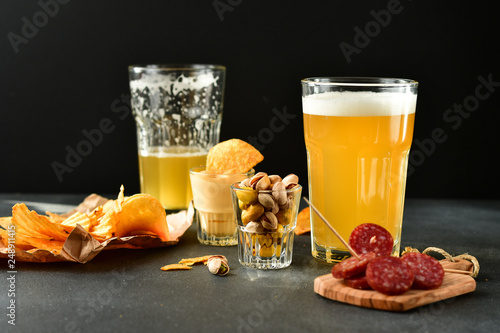 two glasses of beer and snacks chips, nachos with sauce, pistachios and salami, aperitif, relax in the bar with friends, beer party.  selective focus and copy space © Elena