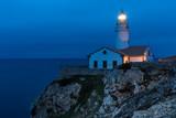 Leuchtturm auf einem Felsen umringt vom Meer, zur blauen Stunde