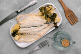 roasted sea bass with potatoes and vegetables on gray marbled background - 248924263