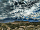 Storm clouds over a desert hill with wind power windmills. - 248930412
