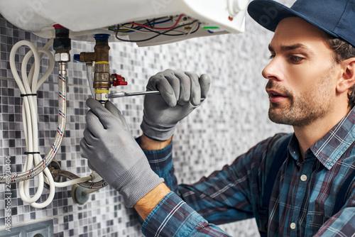 Leinwandbild Motiv Wrench always with you. Worker set up electric heating boiler at home bathroom