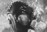 Old used baseball caught in mitt.  Close up view of sports equipment in black and white.