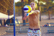 the guy plays volleyball, beats the ball under the net