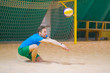the guy is playing volleyball in a covered room with sand. hits the ball