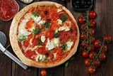 Pizza with tomatoes, mozzarella cheese, black olives and basil. Delicious italian pizza on wooden pizza board. - 248947477