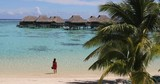 Tahiti luxuy travel resort overwater bungalow hotel in Bora Bora idyllic holiday woman in paradise vertical background with copy space on palm trees. 59.94 FPS SLOW MOTION. - 248960066