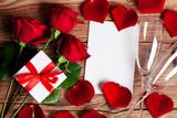 Rote Rosen mit Geschenk und Papier Zettel auf rustikalem Holz Hintergrund