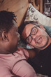 An interracial gay couple talking, lying down in their bedroom.