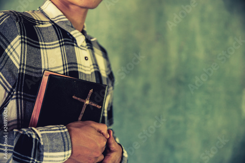 A young man holding a bible in his hands © doidam10