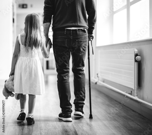 obraz PCV Daughter walking with her disabled father