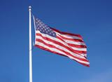 waving USA flag on pole against blue sky - 248994818