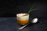lobster bisque with a creamy foam soup topping and garnish on a dark slate background, copy space