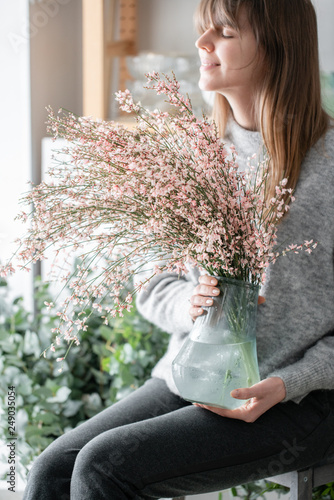 Foto Murales Bouquet in a glass vase of light pink genista cytisus flowers. Pastel color. Spring flowering plant branches. flower shop