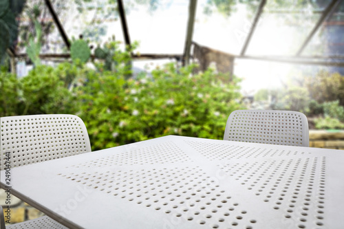 White table of free space with two chairs and spring garden background.