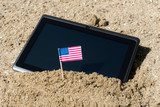 Vacation concept, with a tablet on the beach with the flag of  the USA