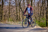 Sports cyclist rides along a trail in the forest on a spring sunny day. - 249049801