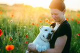 Woman with a dog in sunset