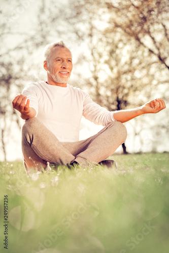 Cheerful mature man enjoying meditation in park