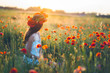 Woman at a flower field in summer sunset