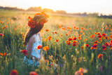 Woman at a flower field in summer sunset - 249058678