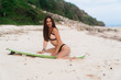 Brunette sexy girl in swimsuit sits on sandy beach with surfboard