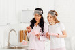 beautiful multicultural girls in sleeping masks and pajamas opening gift boxes in kitchen
