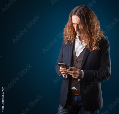 Foto Murales long-haired stylish man with smartphone in jeans and jacket on a blue background. Studio photography
