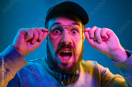 Enjoying his favorite music. Happy young stylish man in sunglasses with headphones screaming while standing against blue neon background