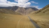 Wide aerial shot in the Himalayan mountains, light traffic on an asphalt road