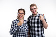 Nerds, geek, bespectacled and funny people concept - a couple of nerds in glasses show us thumbs up on white background