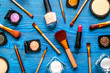 set of decorative cosmetics on blue table background top view