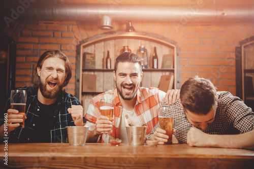 Foto Murales Men watch game on TV screen in pub, drinking beer, shouting and cheering for players