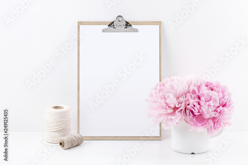 Leinwanddruck Bild clipboard mock up with blank sheet of paper (DIN A4, portrait format), two yarn spools and a bunch of pink peonies on a white table - copyspace for design or text