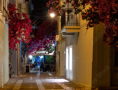 View of a street and cafe in Nafplio, Greece, at night decorated with flowers and vines