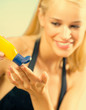 Young happy smiling beautiful tanned woman applying sun protection cream on sea beach