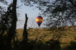 Hot air balloons flying over rural Iowa landscape