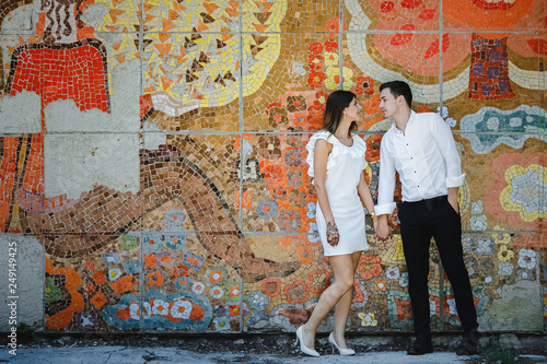 www.Young couple standing over colorful wall background.