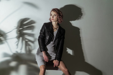 beautiful woman with makeup and short pink hair in grey dress and black leather jacket posing on grey background with dark shadow of leaf texture pattern. indoor studio shot. © khosrork