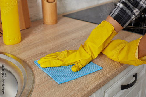 c1c9f2aad0192 Hands in gloves with green rag is cleaning kitchen cabinets - housework and housekeeping  concept