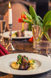baked beef with baby patizone, sauce and spinach served on white plate with flowers and champagne, romantic time on valentines day - 249178428