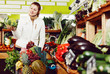 Woman looking for vegetables in farmers market - 249182063