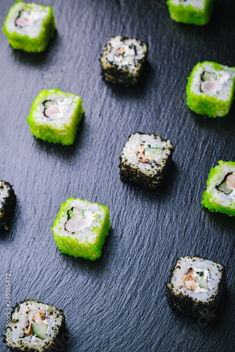 sushi rolls with wasabi, soy sauce, ginger, chopsticks and teapot on black stone background